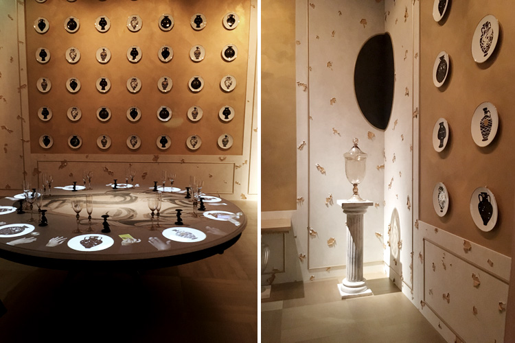Convivium: gold is the dominant note of the dining room. The enviroinments is brought to life by a projection of moving hands on the round table that create contrast with porcelain plates on the walls.
